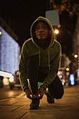 Female runner tying shoelace on urban sidewalk at night