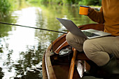 Man fly fishing and using laptop with coffee in a boat