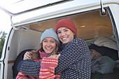 Happy young women friends hugging outside camper van