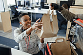 Businesswoman receiving lunch bag from courier in office