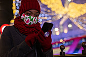 Woman in Christmas face mask and scarf using smartphone