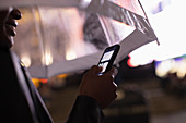 Young woman using smartphone under umbrella at night
