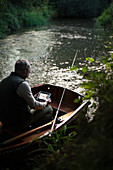 Man fly fishing and video chatting with a tablet in boat
