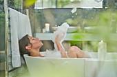 Woman having a bubble bath in luxury soaking tub