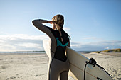 Female surfer with surfboard looking away on sunny beach