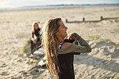 Carefree young female surfer in wet suit on sunny beach