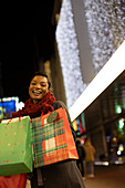 Happy young woman with Christmas shopping bags in city