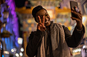 Happy young woman taking selfie gesturing peace sign