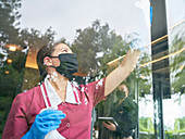 Female hotel maid in face mask cleaning hotel window
