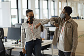 Business people in face masks elbow bumping in office