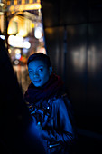 Young woman in dark light at night