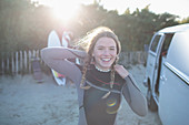 Happy young female surfer in wet suit outside sunny van