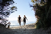 Female surfers walking with surfboards on sunny beach path