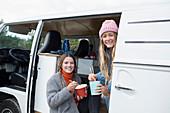 Happy young women friends eating instant noodles in van