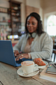 Woman using laptop next to cappuccino and croissant in cafe