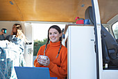 Happy young woman with coffee using laptop in camper van
