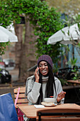 Woman talking on smartphone and eating lunch on cafe patio