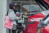 Young woman loading groceries into hatchback of car