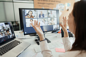 Woman video conferencing with coworkers at computer screen