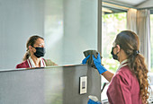 Hotel maid in face mask and gloves cleaning bathroom mirror