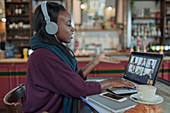 Young woman with headphones video chatting with colleague