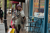Young woman with shopping bag talking on smartphone