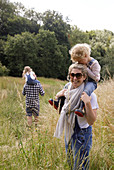 Happy mother carrying daughter on shoulders in rural field