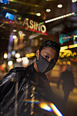 Confident young woman in facemask on city street at night