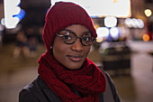 Confident young woman in eyeglasses scarf and hat at night