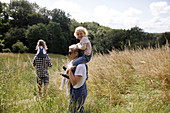 Happy girl on shoulders of mother in sunny rural field