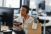 Confident businesswoman eating takeout lunch at office desk