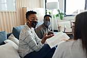 Business people in facemasks discussing paperwork in meeting