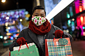 Happy young woman in Christmas facemasks shopping at night