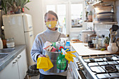 Confident woman in facemask with kitchen cleaning supplies