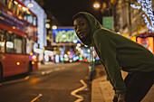 Female jogger waiting to cross street at night, London, UK
