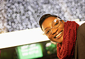 Happy young woman in funky eyeglasses and scarf below lights