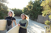 Happy young female surfers carrying surfboards on beach path