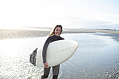 Happy young female surfer with surfboard in sunny ocean surf