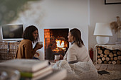 Mother and daughter with tea talking at fireplace