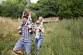 Happy parents carrying daughters on shoulder in tall grass