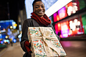 Happy woman with Christmas gift on city street at night