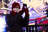 Woman in Christmas mask taking selfie among city lights