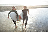 Happy young female surfers running with surfboards on beach