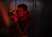 Young woman using digital camera in dark red light