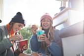 Happy young women eating instant noodles in camper van