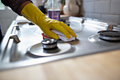 Woman in rubber gloves cleaning kitchen stove with rag