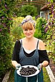 Proud woman with fresh harvested blackberries in garden