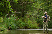 Man casting fly fishing pole at remote green river