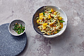 Vegan pointed cabbage salad with red lentils, oranges and pine nuts