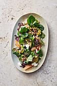 A salad with grilled avocado, lamb's lettuce, grapefruit and feta cheese